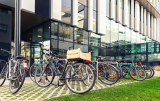 Bikes parked outside a modern apartment residential buiding.